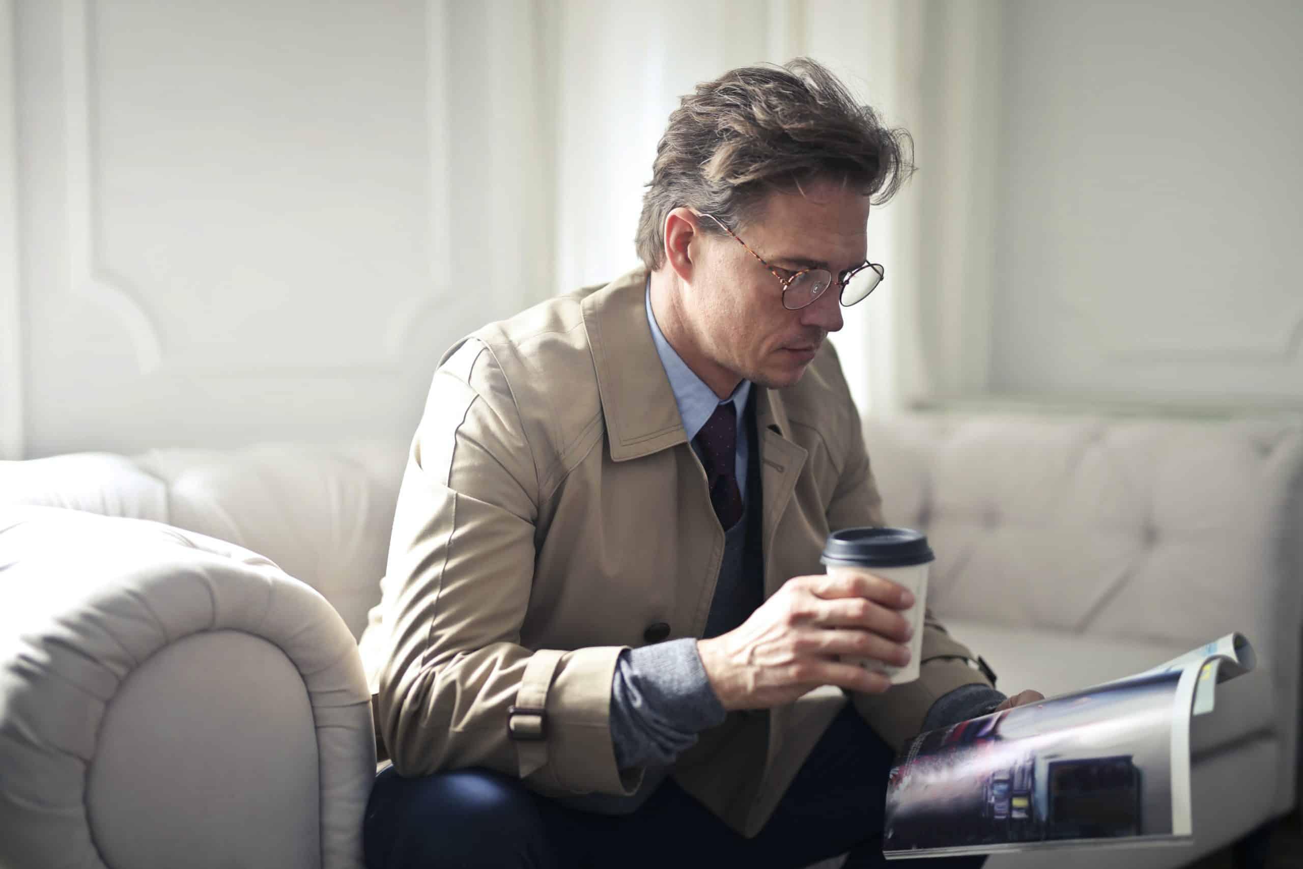 Homme assis buvant un café dans un gobelet jetable