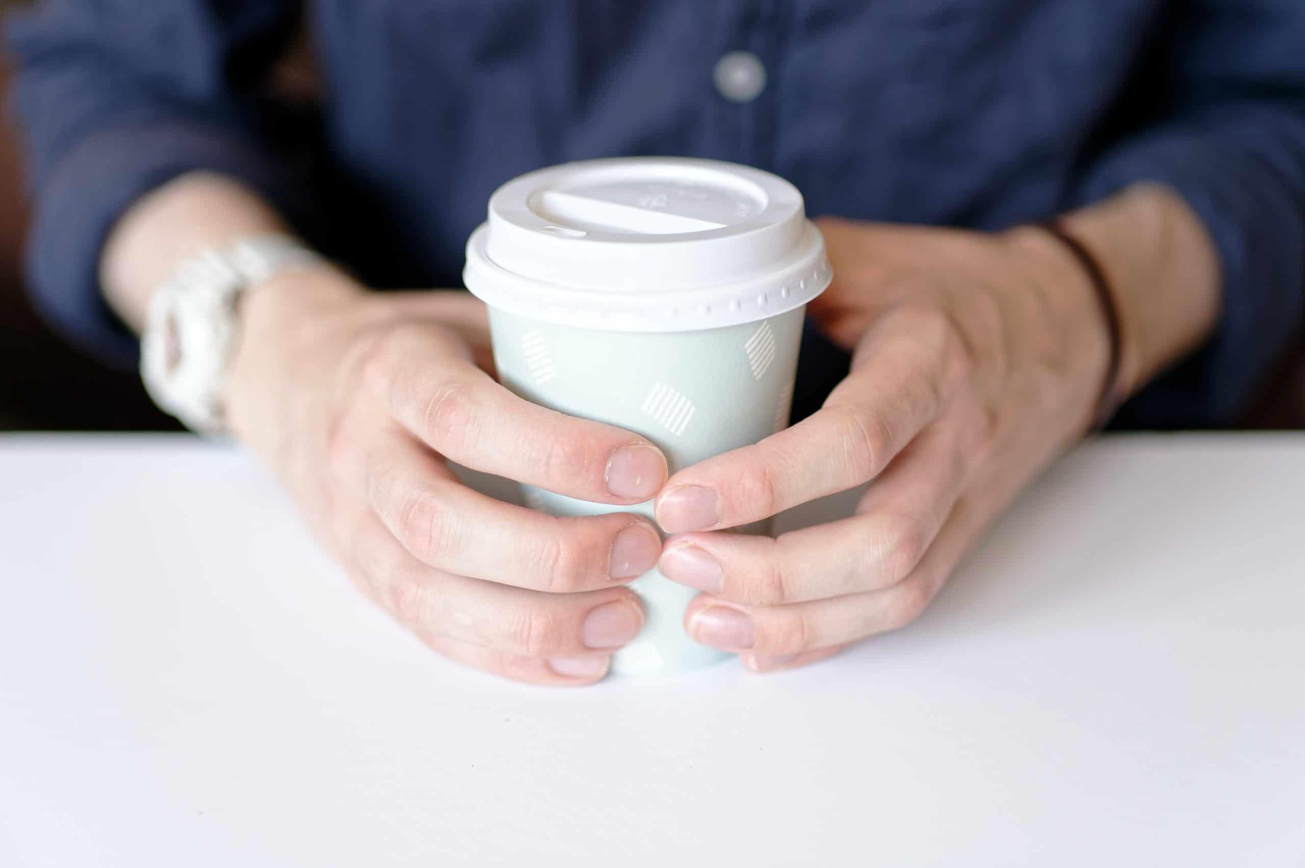 Gobelet en carton entre les mains